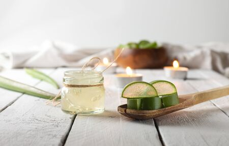 Sliced Aloe Vera and glass jar on white wooden background with candles