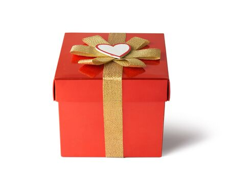 Gift for Valentine's Day, wrapped in red wrapping paper with golden bow, white background Stock Photo