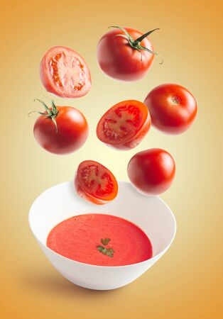 Fresh tomatoes flying, homemade tomato cream bowl, crushed tomato, yellow isolated background. flying vegetables concept Stock fotó
