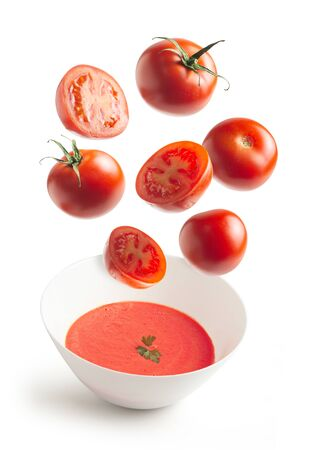 Fresh tomatoes flying, homemade tomato cream bowl, crushed tomato, white isolated background. flying vegetables concept