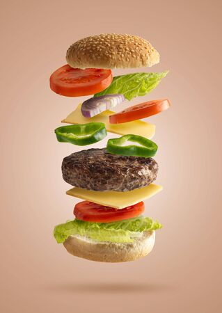 hamburger sandwich flying with vegetable ingredients, isolated from the beige background, lettuce, onion, tomato, cheese, green pepper