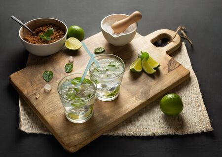 Caipirinha of Cachaça, Mojito of white rum, lime, fresh mint, brown sugar and crushed ice. Rustic environment with black background