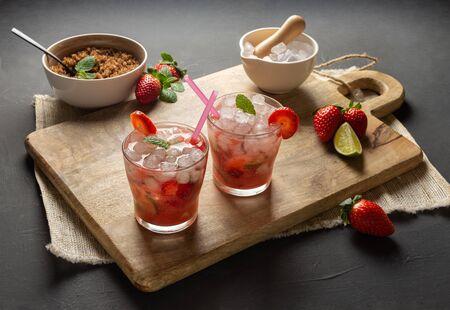 Strawberry Caipirinha, lime, fresh mint, brown sugar and crushed ice. Rustic environment with black background Zdjęcie Seryjne