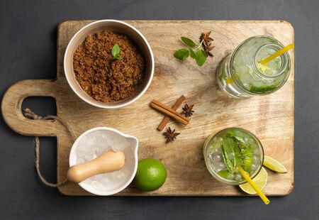 Caipirinha, lime, fresh mint, brown sugar and crushed ice. Rustic environment with black background. Aerial View Banque d'images - 138389233