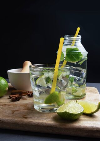Cachaca caipirinha with lime and chopped ice, space for copying, dark brown sugar and fresh mint, vertical composition