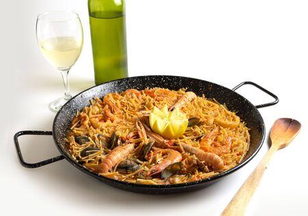 seafood fideua on white background traditional food, handmade, spanish gastronomy