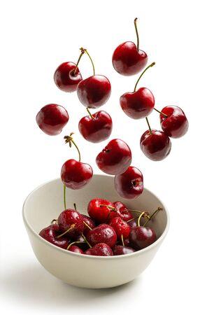 cherries flying in white bowl isolated from background, fresh seasonal cherries 写真素材
