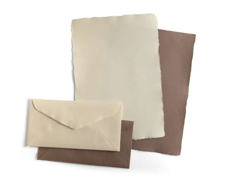 Sheets of paper and envelopes handmade natural beige, isolated from the background. Imagens