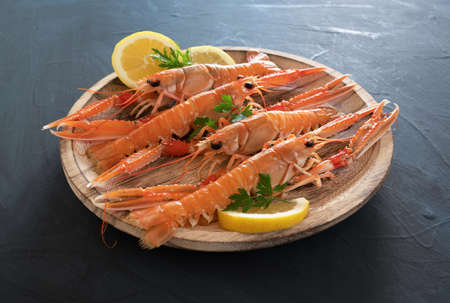 plate of fresh Norway lobsters on rustic background