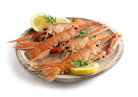 Fresh Norway lobster on wooden plate, isolated from white background Reklamní fotografie