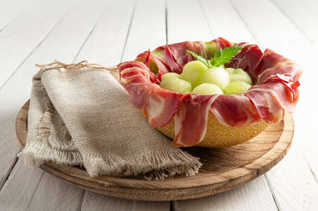 melon with air dried ham, served in halved melon stuffed with serrano ham and melon balls. on white wood background 版權商用圖片