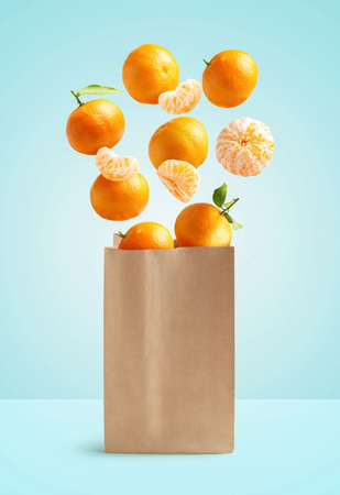Flying tangerines, recyclable paper bag, isolated from the blue background