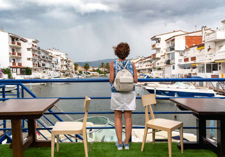Woman contemplating beautiful canal side houses with moored boats on a cloudy day