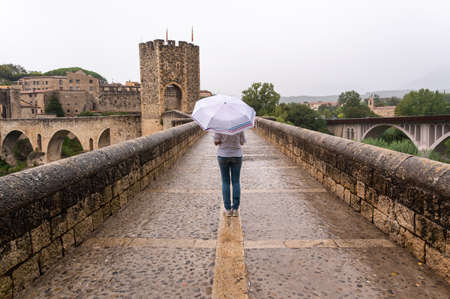 Woman with umbrella in the rain on a bridge in a medieval village