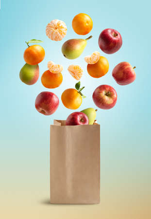 Fresh fruits flying out of a recyclable paper bag