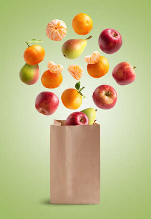 Fresh fruits flying out of a recyclable paper bag. isolated from green background Stock fotó