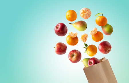 Recyclable paper bag with fresh fruits flying out, copy space blue background Stock fotó