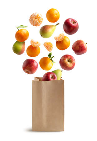 Fresh fruits flying out of a recyclable paper bag. isolated from white background