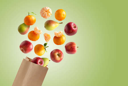 Recyclable paper bag with fresh fruits flying out, copy space green background Stock fotó