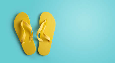 Yellow flip-flops on a blue background with space for your text. summer concept