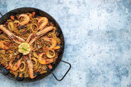 Seafood fideua on blue rustic background, top view Banco de Imagens