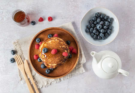 Homemade pancakes with fresh blueberries, raspberries and honey. top view
