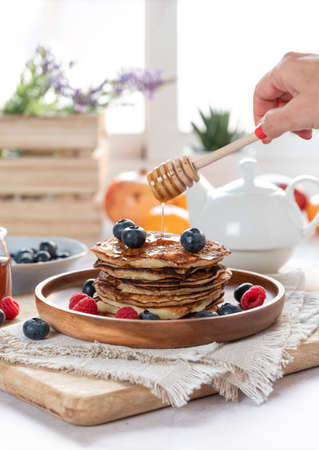 Woman pouring honey onto tasty pancakes with fresh blueberries, raspberries and honey 스톡 콘텐츠