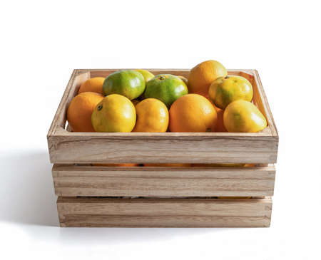 Wooden box with fresh seasonal tangerines isolated from the white background