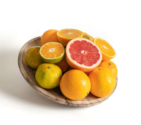 Wooden plate with fresh seasonal fruits isolated from the white background
