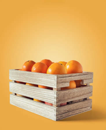 Fresh oranges in a wooden box, isolated from the orange background whit copy space Stock fotó