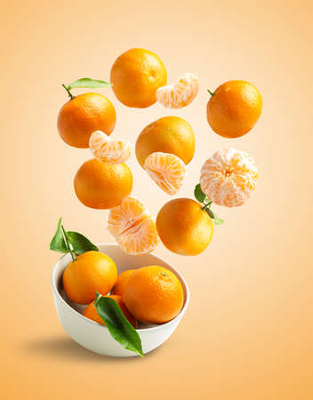 Tangerines flying in a bowl on orange background