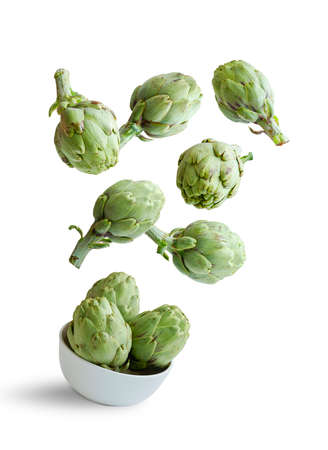 Flying artichokes in a bowl isolated from the white background