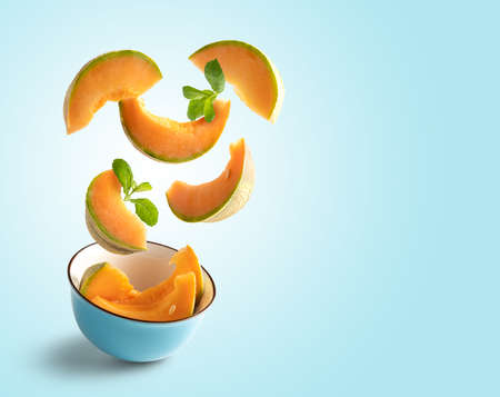 Cantaloupe slices flying on blue blue background with copy space 版權商用圖片