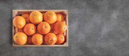 Fresh oranges in wooden box with stone background with copy space