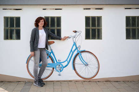 middle-aged woman with bicycle painted on a wall Reklamní fotografie
