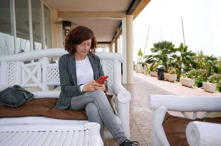 middle-aged woman sitting on a terrace using her smart phone