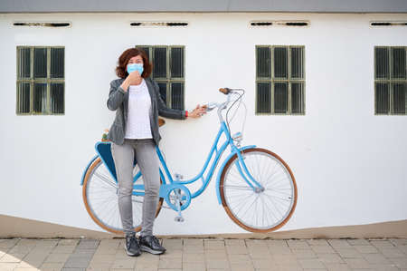 middle-aged woman with face mask leaning against a wall with painted bicycle