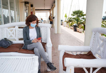middle-aged woman with face mask seated using her smart phone
