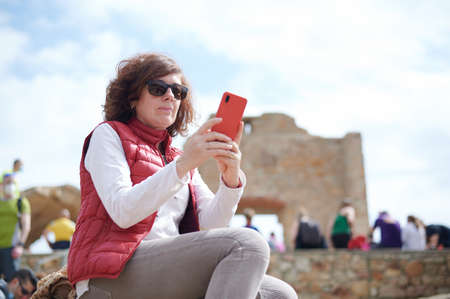 middle-aged woman taking a selfie in a tourist place
