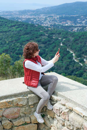 Woman taking pictures with her smart phone in a mountain lookout