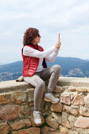 Woman making a selfie with her smart phone in the mountain