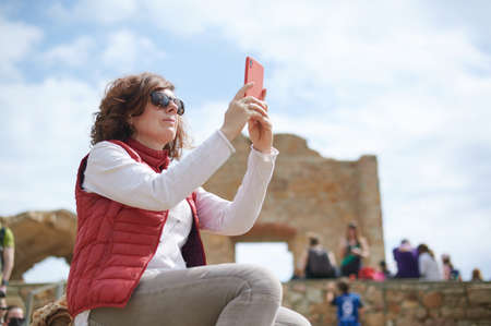 Middle-aged woman taking photo with her smart phone in archaeological ruins