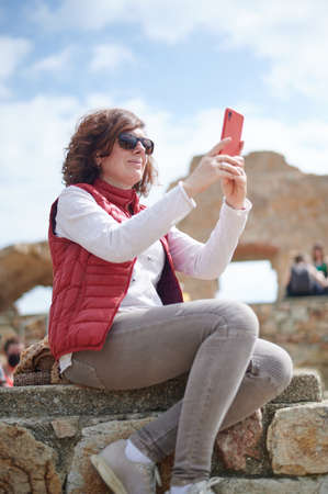 Middle-aged woman taking photo with her smart phone in outdoors with copy space Reklamní fotografie - 167274524