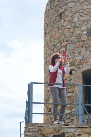 Woman taking photo with her smart phone in archaeological ruins