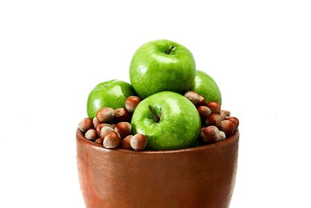 A brown earthenware bowl filled with green Granny Smith apples and brown hazelnuts isolated on white background.