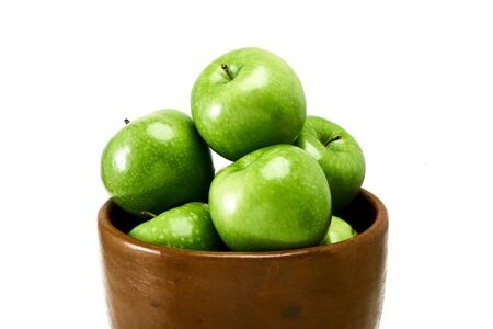 A group of Green Granny Smith cooking apples in a brown bowl isolated against a white background.