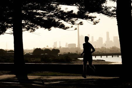 Early morning male jogger silhouetted against the skyline of the city of Melbourne, Australia. 写真素材