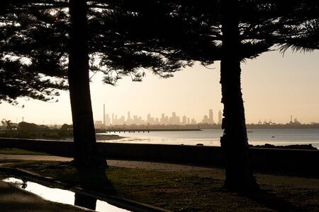 A view of Melbourne, Australia skyline photographed from Altona Beach and framed by a couple of trees.