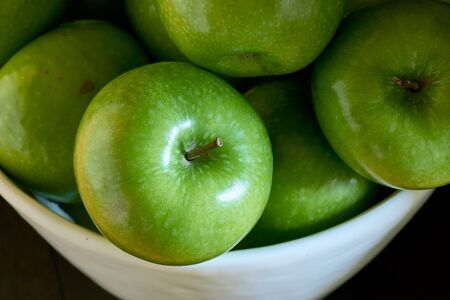 A close-up image of a group of green Granny Smith cooking apples in a white bowl from above.