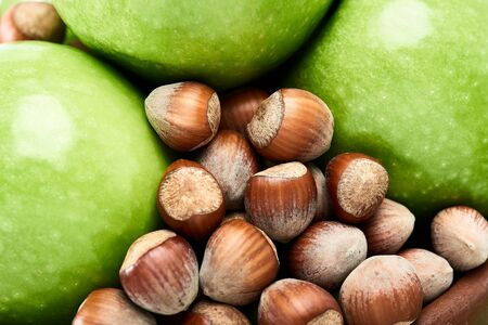 Brown hazelnuts and vibrant green of fresh Granny Smith apples close-up.